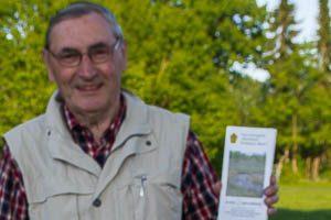 Auf der Moorführung zeigt Herr Behnke das Informationsblatt Tävsmoor